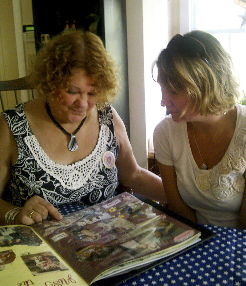 Magi Bish, left, looks at a scrapbook of remembrances of her slain daughter, Molly Bish, with Molly's older sister, Heather. State police spent two days last month questioning a Florida inmate in Molly's death. Investigators have sent evidence for a new round of DNA testing, and prosecutors plan to ask the FBI's behavioral analysis unit to review the 2000 case.