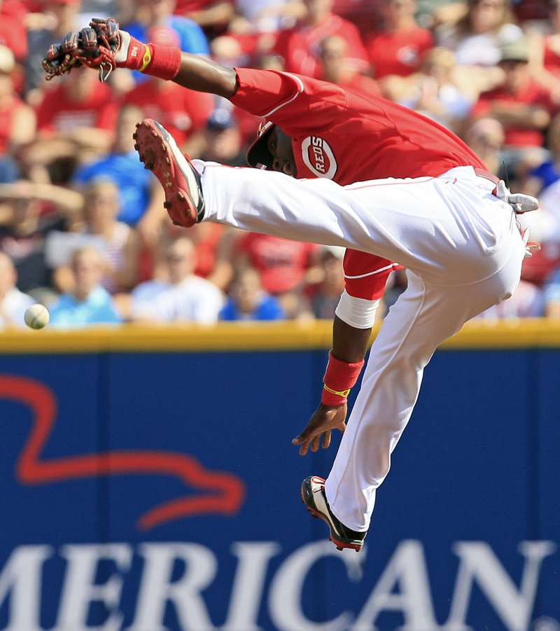 Cincinnati's Brandon Phillips makes a high-flying but unsuccessful leap at a hit by the Cardinals' Skip Schumaker during the Reds' 8-2 win Saturday at Cincinnati.