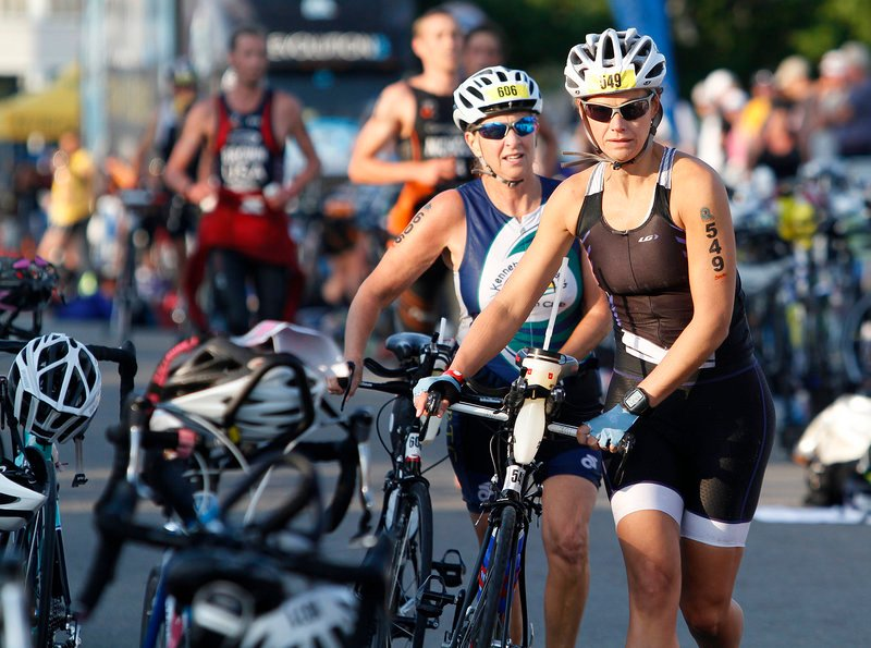 Dava Davin of Cumberland Foreside and Mary Hebert of Kennebunk, in back, leave the first transition area with their bikes during the event, which drew 1,100 competitors.