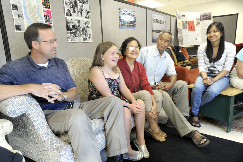 Abbie Jacobson, 8, of Scarborough sits next to her now-close friend Ra Rim, an immigrant from Cambodia, at Southern Maine Community College on Monday, along with Abbie's dad John Jacobson, left, Ra's husband San Meas and her daughter Chansatha.
