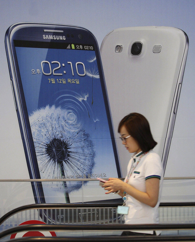 A woman walks by a sign advertising Samsung's mobile phone Galaxy III at the company's headquarters in Seoul.