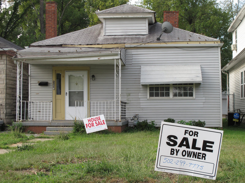 For-sale signs dot the front lawn of Muhammad Ali's boyhood home Monday in Louisville, Ky.