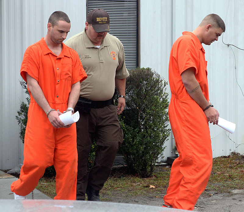In this Dec. 12, 2011, file photo, Army Pfc. Michael Burnett, 26, right, and Pvt. Christopher Salmon, 25, are led away in handcuffs after appearing before a magistrate judge at the Long County Sheriff's Office in Ludowici, Ga.