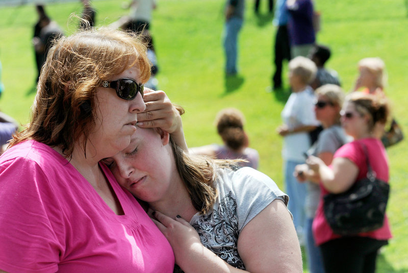 Tracie Bradford of Perry Hall, Md., consoles her daughter Leah, a student at Perry Hall High School who said she was in the school's cafeteria when a student was shot there and critically wounded on the first day of classes Monday.