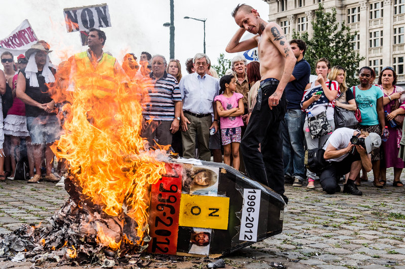 Demonstrators gather around a burning mock coffin with the pictures of Belgian child killer Marc Dutroux and his ex-wife, Michelle Martin, during a march this month in Brussels to remember their victims.