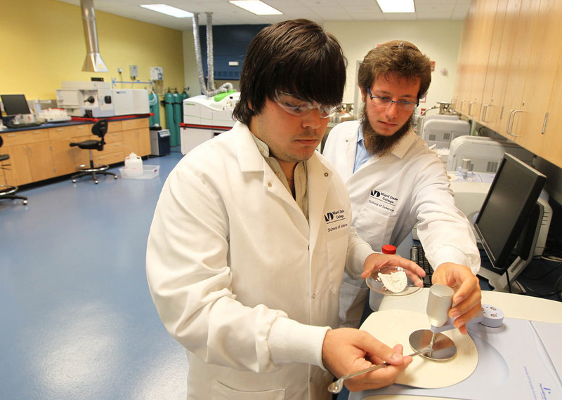 Gabriel Pacareu and Benjamin Eisenman work with an infrared spectrometer in a lab at Miami-Dade College's School of Science, where classes focus on skills students can use in the medical industry.