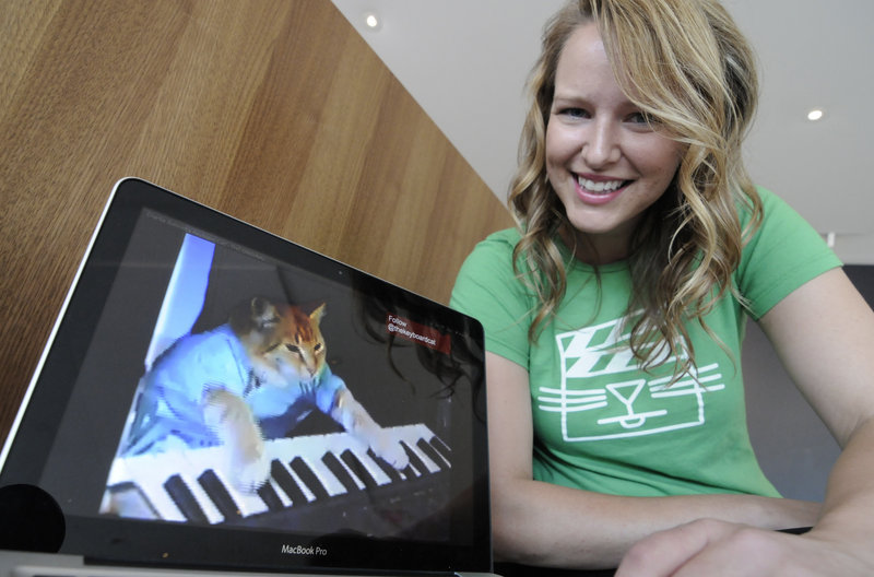 "Katie Hill, a program associate with the Walker Art Center n Minneapolis shows a frame from a video of a cat playing the piano. The Walker will present its first ""Internet Cat Video Film Festival"" to showcase the best in filmed feline hijinks."