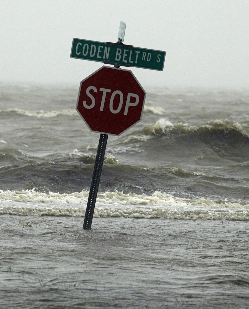 Waters of the Mississippi Sound surround a traffic sign along Coden Belt Road in Coden, Ala.