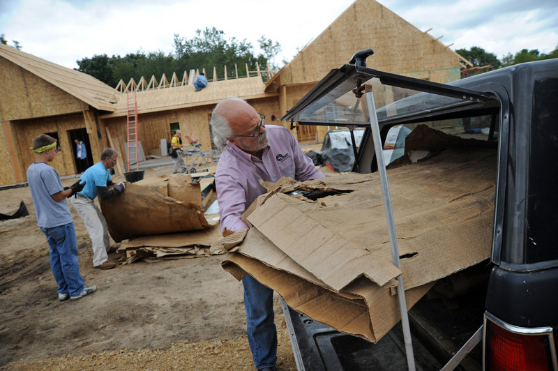 Kelly Cain, director of the St. Croix Institute for Sustainable Community Development, loads cardboard from the construction site in Eco-Village to be shredded for garden mulch in the high-efficiency residential development.