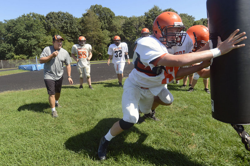 Biddeford football coach Scott Descoteaux looks on as linemen, including Kevin Descoteaux, go through a drill in practice. Biddeford was winless last season and there was concern it influenced a decision to drop to Class B. But enrollment was the factor, and the Tigers will stay in Class A.