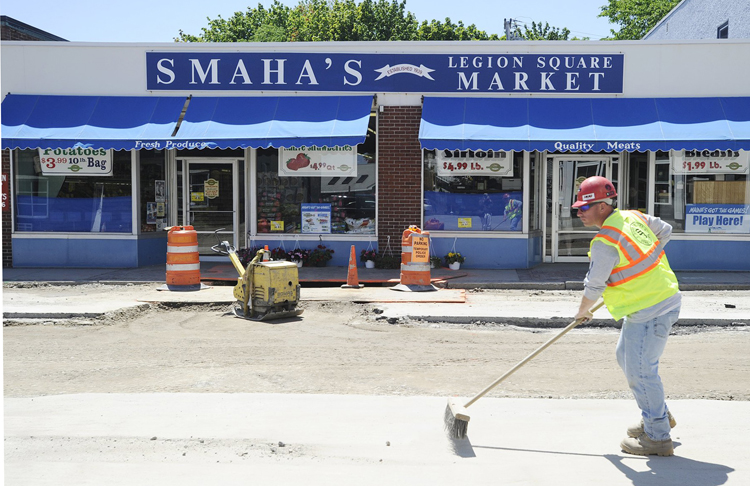 Mike Stuart of Shaw Brothers Construction sweeps the street in front of Smaha's Legion Square Market in this June 14, 2012 photo.
