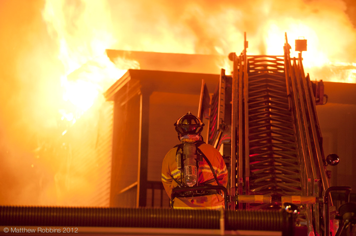 A firefighter helps battle the blaze Wednesday at 554 Main St. in South Portland.