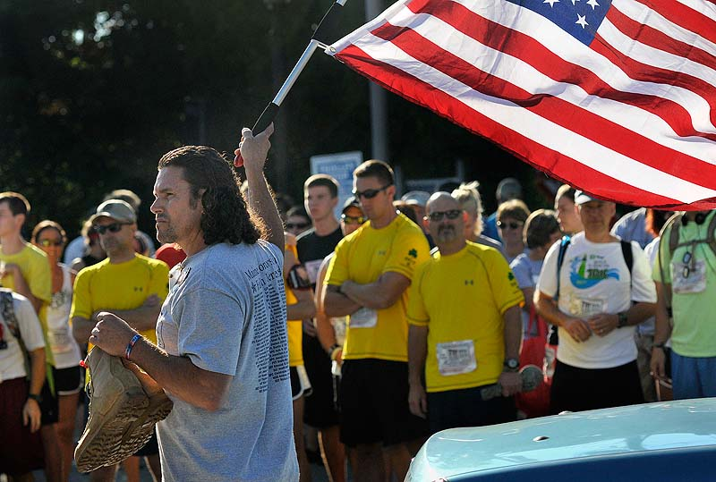 Carlos Arredondo of Boston waves the starting flag, while holding the boots of his late son Lance Cpl. Alexander Arredondo, at the Run for the Fallen in Ogunquit on Sunday. His son died while serving in the Marine Corps in Iraq in 2004.