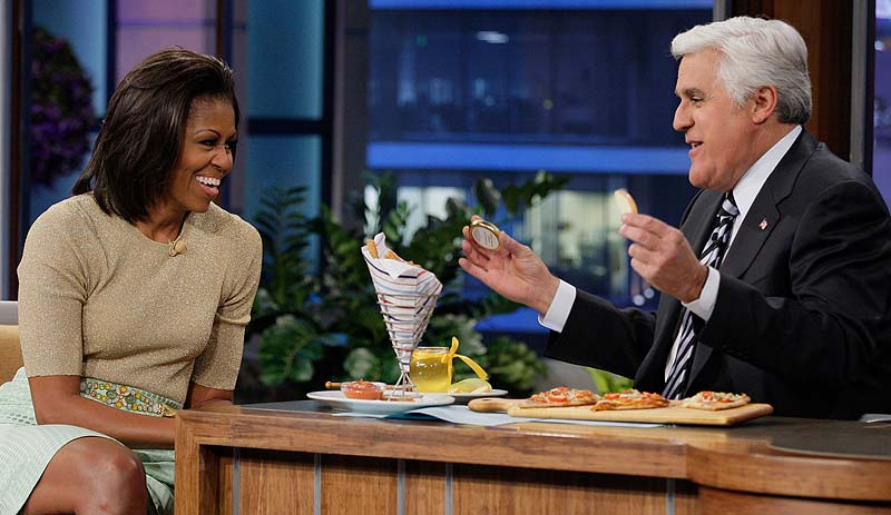 Tonight Show host Jay Leno, speaking with first lady Michelle Obama in January, will be taking a severe pay cut to stave the jobs of his staffers. NUP_148189_0120.jpg;2010s; 2011-2012; Air Date 01/31/2012; Color