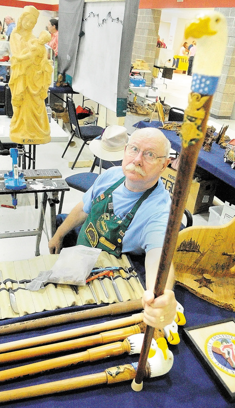 Chuck Friis, president of the Poland Springs chapter of the Maine Wood Carvers Association, shows one of the eagle canes made by chapter members to honor veterans.