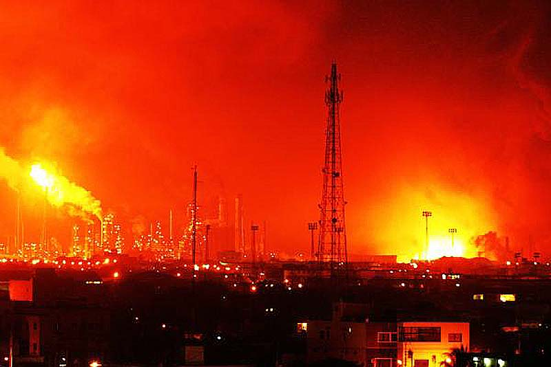 Fire rises over the Amuay refinery near Punto Fijo, Venezuela, Saturday. A huge explosion rocked Venezuela's biggest oil refinery, killing at least 24 people and injuring dozens, an official said.