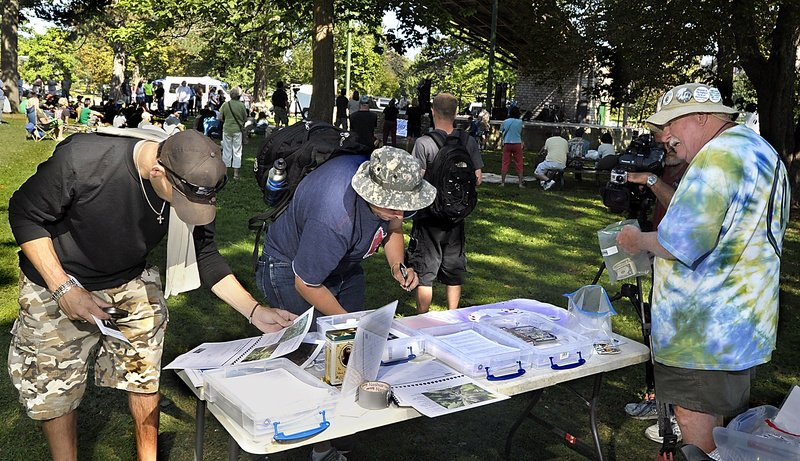Visitors to the Atlantic CannaFEST at Deering Oaks on Saturday listened to music, speakers and promotions of medical marijuana. Here, visitors look at a calendar filled with photos of marijuana and information and sign a petition concerning medical marijuana at a table run by Medical Marijuana Caregivers of Maine. Roger Leisner, right, collects money for buttons and calendar sales to support the effort. Leisner was one of four 2012 winners of Maine Cannabis Awards. He ran the table with Hillary Lister.