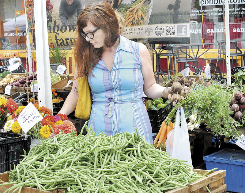 Beth Taylor, of Portland, shops at the Fishbowl Farm stand Wednesday as she and others shoppers visit the Farmers Market at Monument Square in Portland.