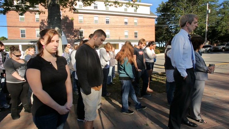 In memory of the Sept. 11, 2001, terrorist attacks, freshman Alli Buck, left, stands with other students and staff during a moment of silence at Southern Maine Community College in South Portland on Tuesday.