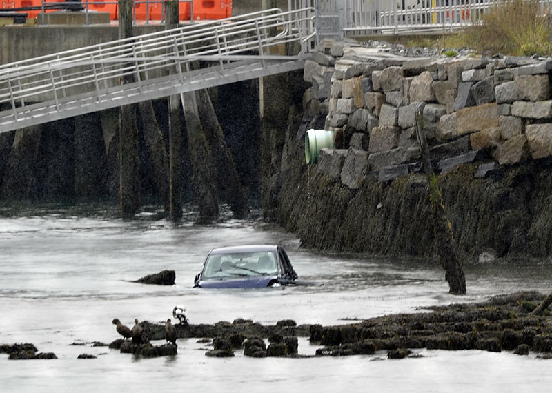 A car is semi-submerged in the water near Ocean Gateway in Portland at the end of India Street.