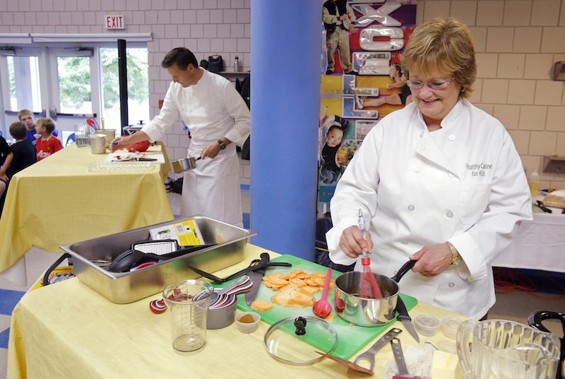 Ellen Demmons, right, food services director for RSU 21 and Jonathan Cartwright, executive chef at the White Barn Inn, compete in an Iron Chef-type competition at Sea Road School in Kennebunk on Friday, September 28, 2012. The secret ingredient announced at the start of the competition was sweet potatoes and the school's fourth graders from the school were the judges of the chefs' final creations.