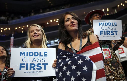 In this Spet. 5, 2012, photo, delegates watch as former President Bill Clinton addresses the Democratic National Convention in Charlotte, N.C. The placards on display as Clinton addressed the DNC said,