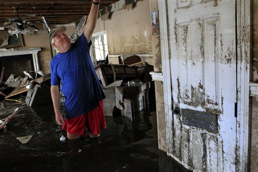 Don Duplantier walks through his flooded home as water recedes from Hurricane Isaac in Braithwaite, La., Sunday, Sept. 2, 2012. In the foreground is a sign marking the waterline from Hurricane Katrina, but floodwater from Isaac went all the way to the second floor. More than 200,000 people across Louisiana still didn't have any power five days after Hurricane Isaac ravaged the state. Thousands of evacuees remained at shelters or bunked with friends or relatives. (AP Photo/Gerald Herbert)