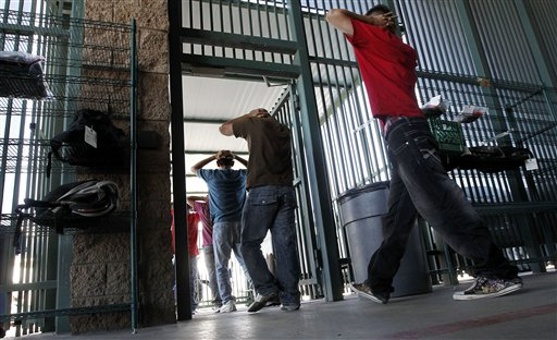 Illegal immigrants prepare to enter a bus after being processed at Tucson Sector U.S. Border Patrol Headquarters recently in Tucson, Ariz.