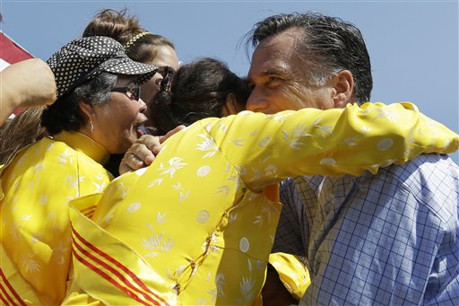 Republican presidential candidate Mitt Romney embraces women wearing traditional Vietnamese