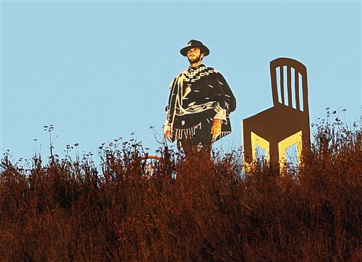 A life-sized cardboard cutout of actor Clint Eastwood next to an empty chair is seen overlooking a freeway in Glendale, Calif., on Tuesday.