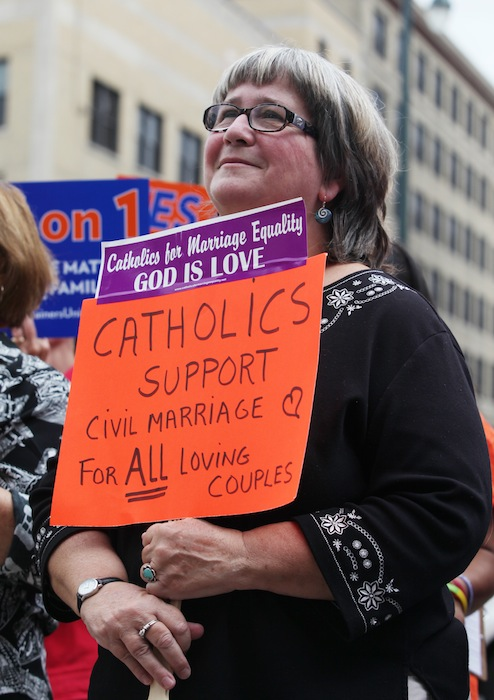 Kathy Tosney holds a sign as she listens to speakers Monday, Sept. 10, 2012 at a rally outside of City Hall in Portland, Maine, in support of a ballot question that seeks to legalize same-sex marriage. (AP Photo/Joel Page)