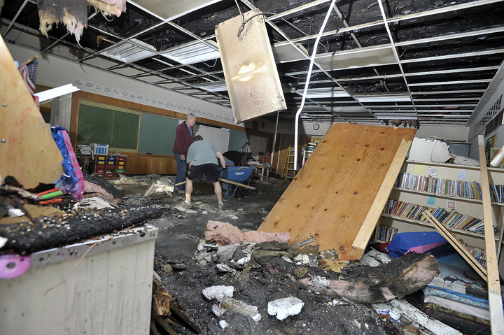 Volunteers, restoration workers and school personnel clean up one of the classrooms damaged by the fire at Hall School on Monday. Firefighters have determined that the fire originated in wiring to an exterior light.