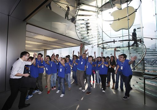A customer cheers with staff members as the Apple store in Hong Kong started selling iPhone 5 on Friday. Apple's Asian fans jammed the tech juggernaut's shops in Australia, Hong Kong, Japan and Singapore to pick up the latest version of its iPhone.