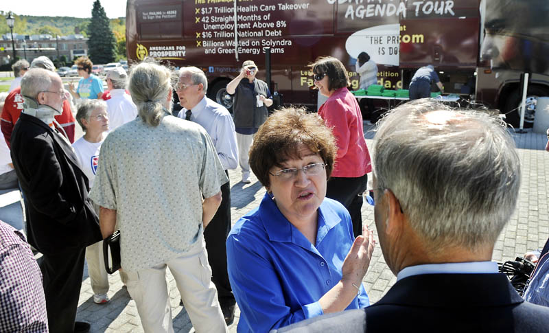 Staff photo by Andy Molloy TOUR: Maine State Director for Americans for Prosperity speaks with Maine State Treasurer Bruce Poliquin Monday during the conservative group's bus tour through Augusta.