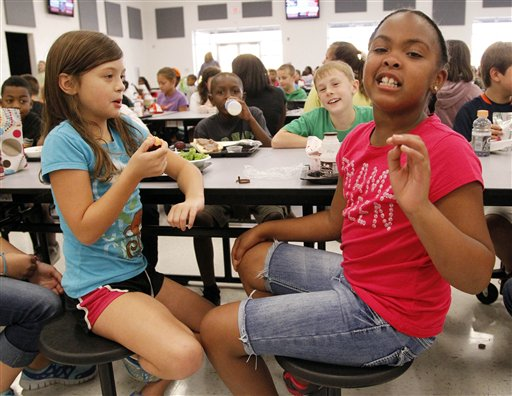 Eastside Elementary school fourth grader Raela Bridges, nine, right, explains what parts of the school lunch she likes to her classmates Grace Bethany, left, Cameron Kinard, back left, and Brock Maddox, back right, all nine, in Clinton, Miss. The Associated Press photo