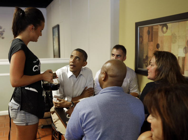 President Barack Obama talks with waitress Megan Emch on as he sits down to have breakfast Monday with local auto workers at Rick's City Diner, in Toledo, Ohio.