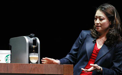 """Hannah So demonstrates a """"Verismo,"""" a single-serving espresso machine, at the annual Starbucks shareholders meeting in this March 21, 2012. photo taken in Seattle."""