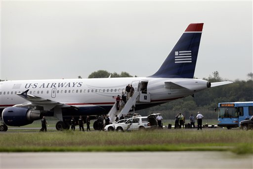 """Passengers walk off a US Airways flight at Philadelphia International Airport on Thursday. An airline spokeswoman says Flight 1267 returned to the airport as a """"precaution."""""""