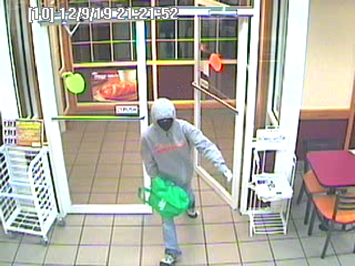 Surveillance image of robbery suspect entering the store. Police say the woman showed a black semi-automatic handgun to employees and demanded cash.