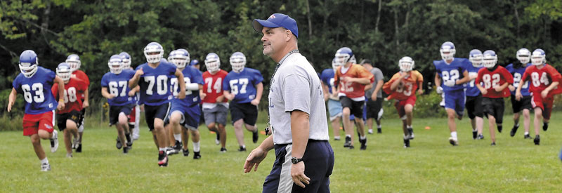 In this Aug. 16, 2010, photo, Messalonskee High School football players begin the first day of practice as then-head coach Wes Littlefield conducts drills.