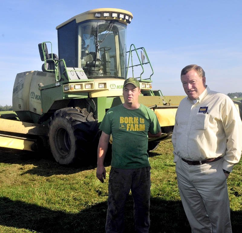 FARM TOUR: Second District Congressional candidate Kevin Raye, right, and Flood Brothers farm employee Jake Owens look over a hay field that was being mowed in Clinton during a campaign stop on Thursday.