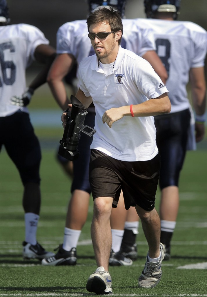 Jimmy Bump, a former quarterback for Cape Elizabeth and now a senior at UMaine, jogs downfield while filming a recent Black Bears practice at Morse Field in Orono.