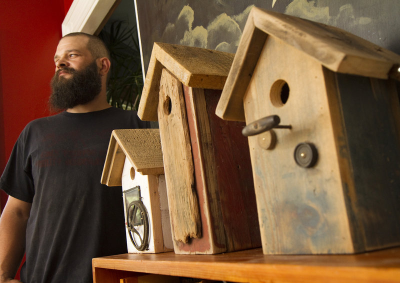 Reuben J. Little with some of the birdhouses he creates in his Portland workshop. He often finds old wood and other materials from doing carpentry jobs.