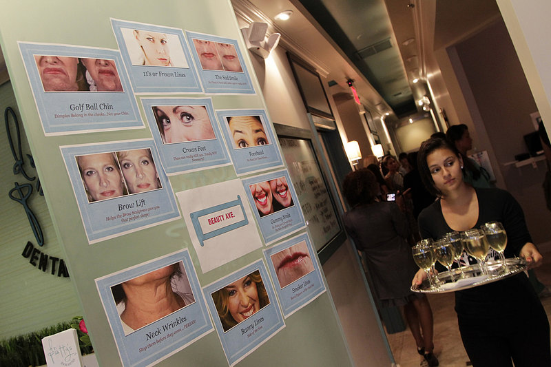 Cosmetic procedures are posted on the door as wine is served during an open house this month at Dr. Patty's Dental Boutique in Fort Lauderdale, Fla. Dr. April Patterson's business offers everything from conventional dentistry to injections and chemical peels.