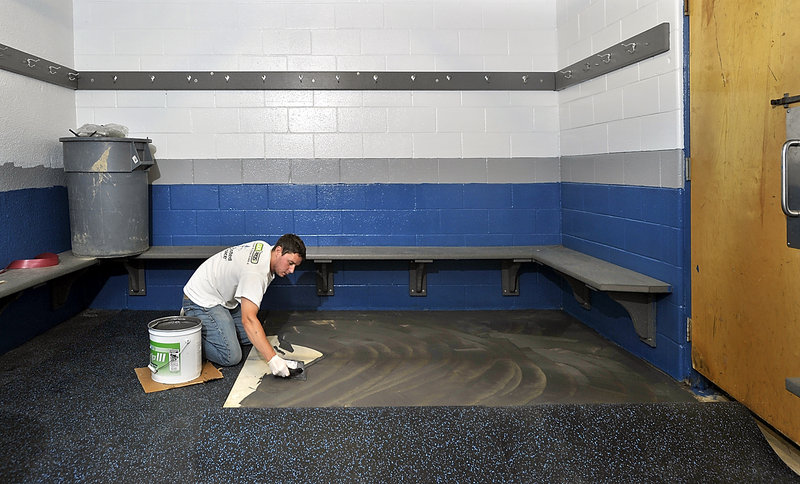 Anthony Reynolds, a Portland Ice Arena employee, spreads glue for new rubber matting in one of the locker rooms of the renovated facility. The arena reopens Tuesday after being closed since May.