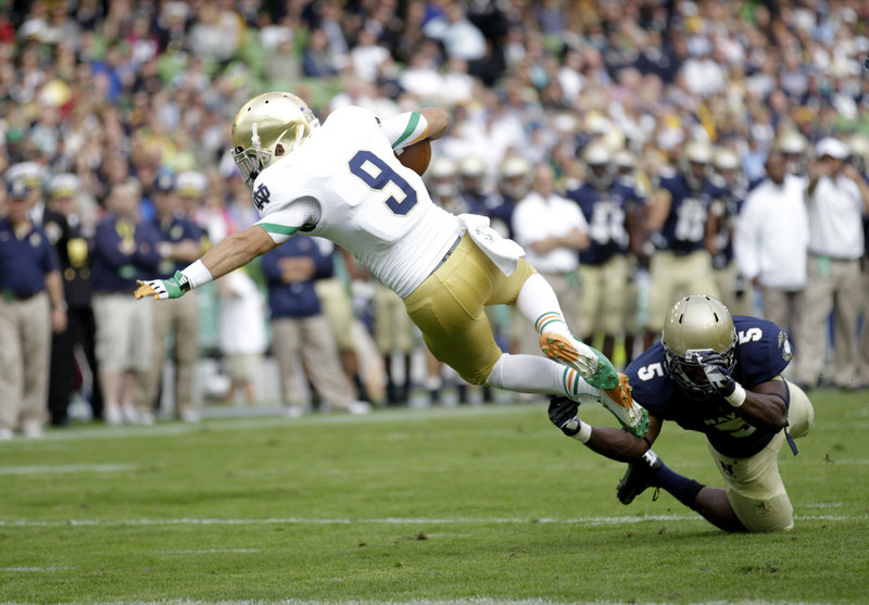 Notre Dame's Robby Toma lunges for the end zone as Navy's Quincy Adams arrives too late to keep him from scoring a touchdown Saturday in Dublin, Ireland. Notre Dame won, 50-10.
