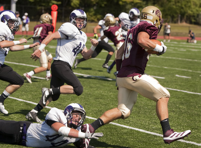 Andrew Libby of Thornton Academy eludes a foot tackle from Dominic Esposito-Martin of Deering to score a second-quarter touchdown on a punt return, giving the Golden Trojans a 17-0 lead Saturday on the way to a 44-14 victory at Saco.