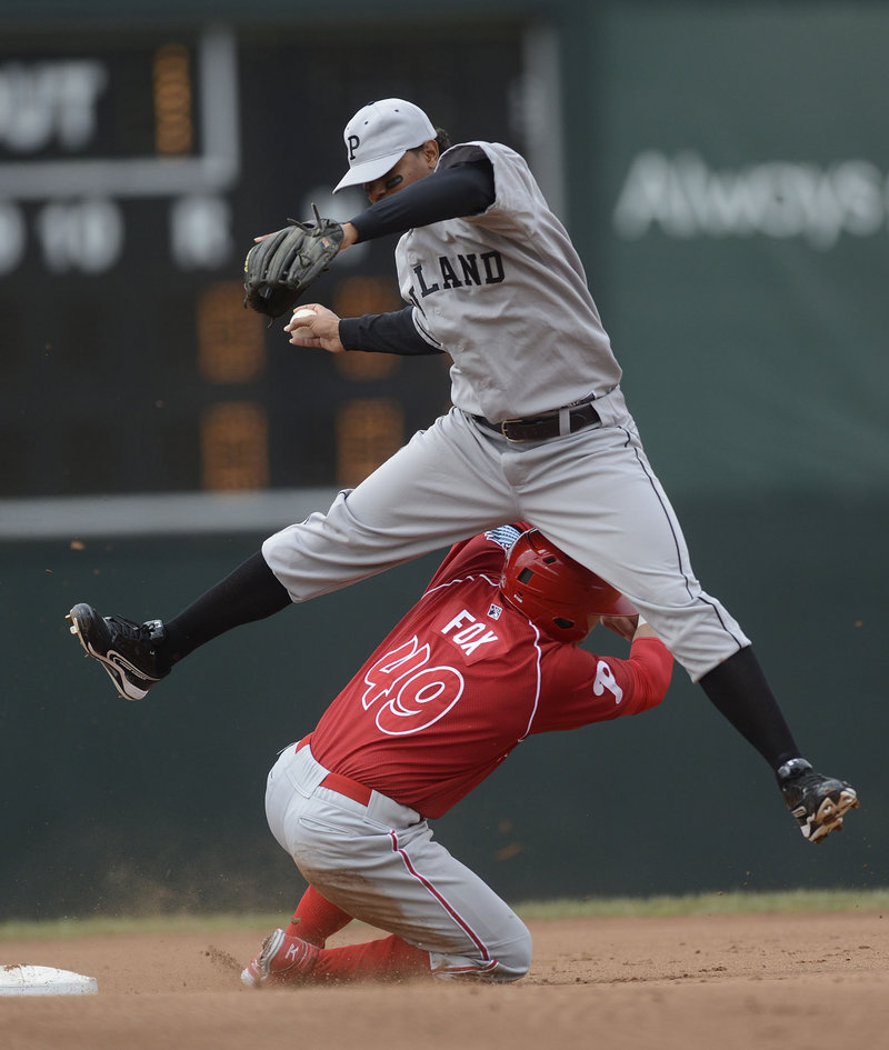 Jake Fox of the Reading Phillies disrupts Sea Dogs shortstop Xander Bogaerts' attempt to turn a double play.