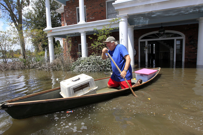 Don Duplantier paddles a pirogue from his flooded home as floodwaters from Hurricane Isaac recede in Braithwaite, La., on Sunday. Duplantier had retrieved his cat and his daughter's bridesmaid dress for his son's upcoming wedding.
