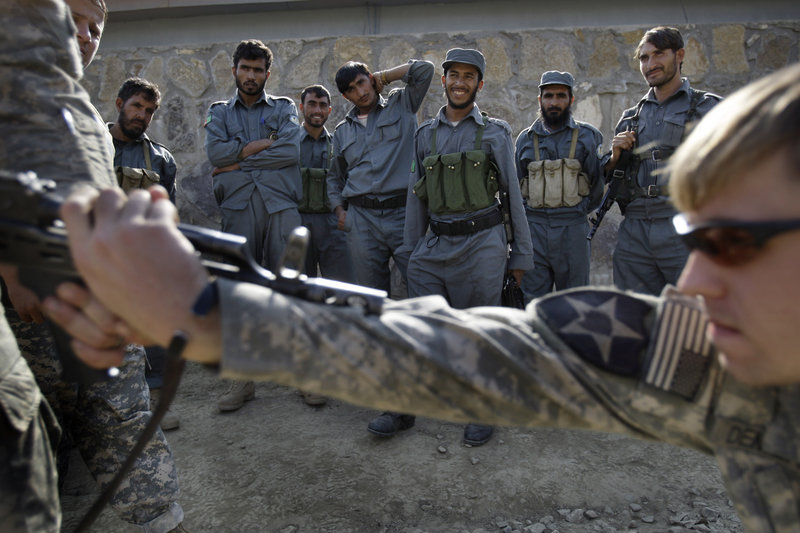 Afghan national policemen look on in 2009 as a U.S. soldier helps train the police on how to apprehend a gunman. The U.S. is reviewing its training program, and making changes, as 45 coalition troops have been killed by insider attacks this year.